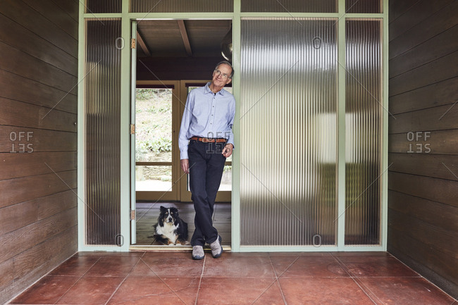 Los Angeles, California - April 13, 2017: Portrait of a man standing in doorway of his home with dog