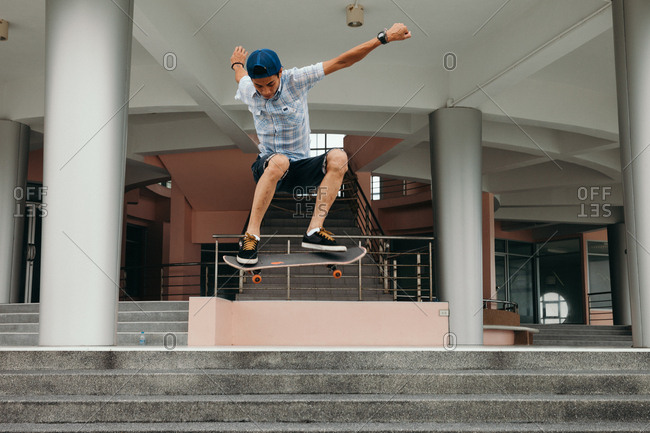 Thailand - August 4, 2014: Boy doing jump on skateboard