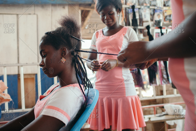 Ghana - January 27, 2015: Woman having her hair braided