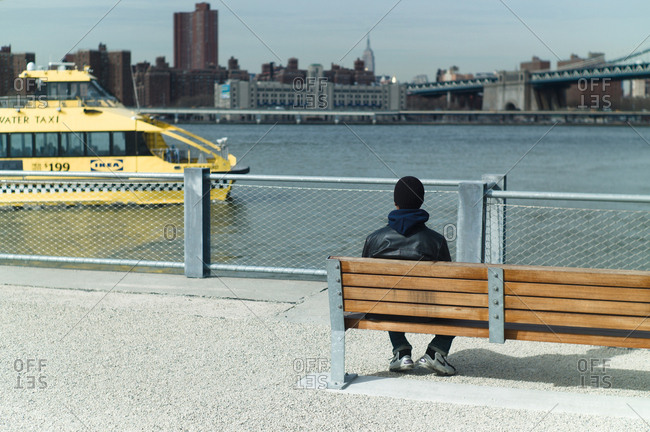 New York City, New York, USA - March 30, 2011: Man sitting on bench overlooking the East River