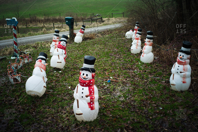 Several snowman decorations on a front lawn