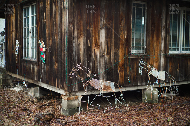 Holiday decorations outside of a house with wooden siding