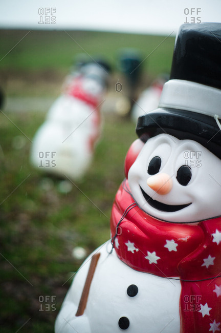 Snowman decorations on a front lawn