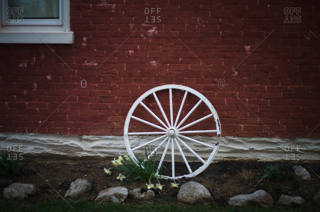 Wagon wheel leaning on red brick home in Ohio