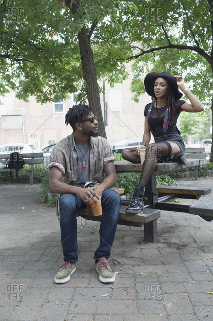A young man and a young woman at a picnic table.
