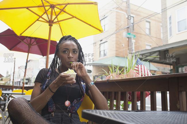 A young woman eating frozen yoghurt.