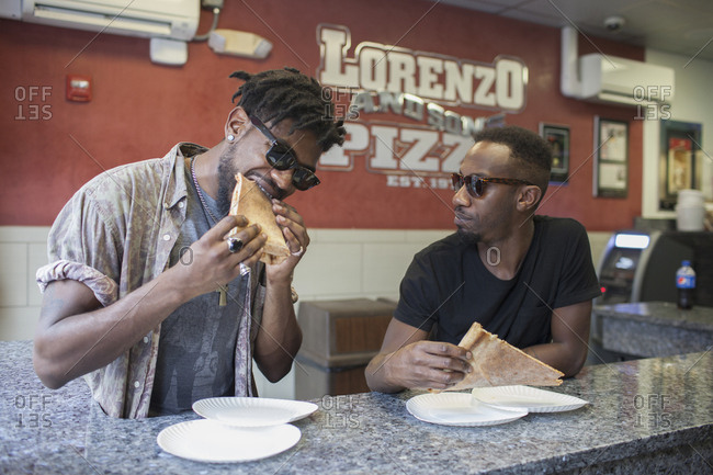 Two young men eating pizza in a restaurant.