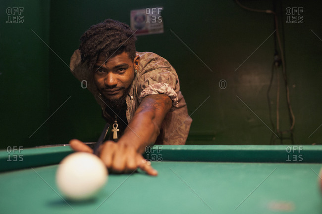 A young man playing pool.
