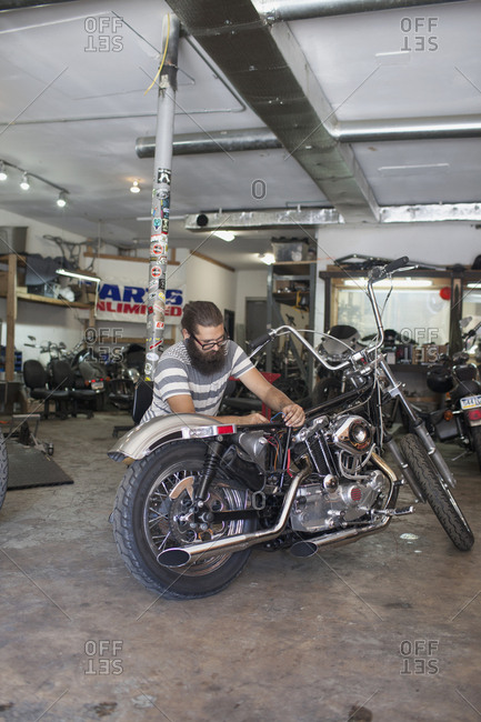 A young man repairing a motorcycle.