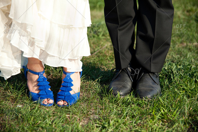 Close up of shoes worn by a bride and groom standing in grass