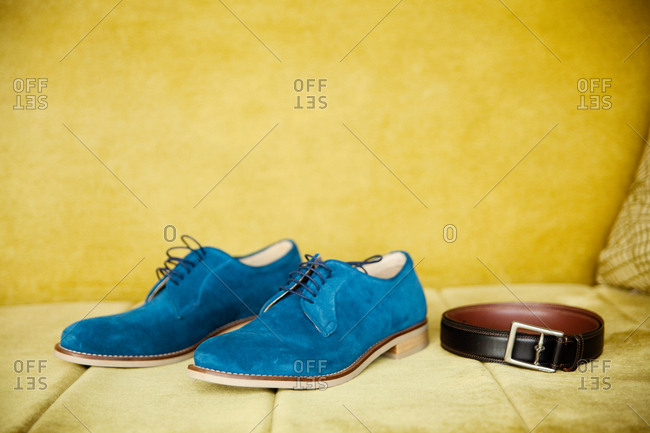 Blue shoes and belt on yellow sofa