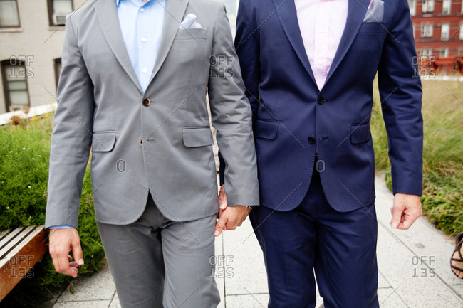 Gay couple standing together in tuxedos