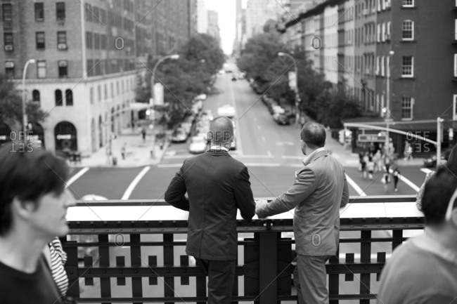 Gay couple in suits overlooking streets in High Line park in NYC