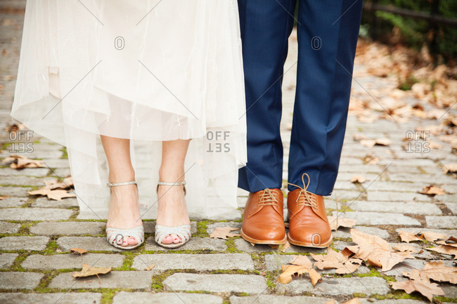 Shoes worn by a bride and groom standing on stone path
