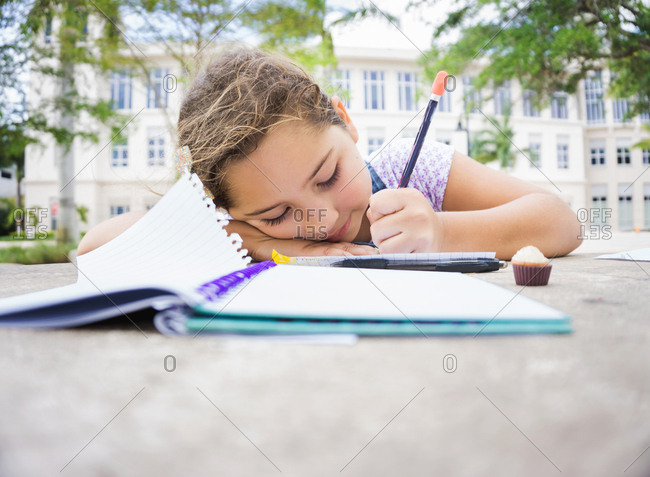 Girl writing in a notebook while resting her head on her arm