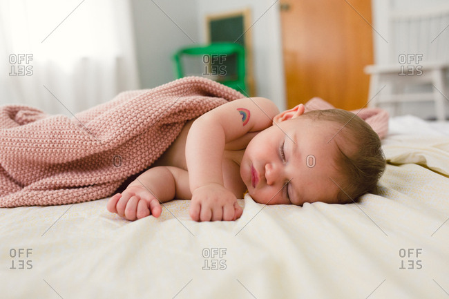 Sleeping baby with a rainbow temporary tattoo on arm