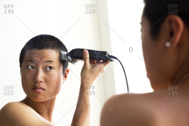 Woman shaving hair while reflecting in mirror