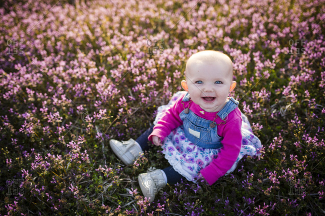 High angle portrait of happy baby girl sitting on field