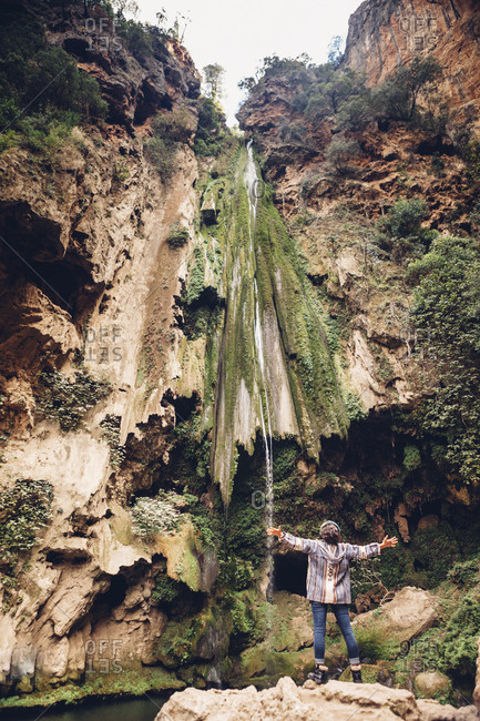 Rear view of female hiker with arms outstretched standing by waterfall over rock formation