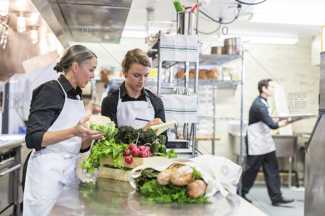 Female chefs examining vegetables while male coworker working in background