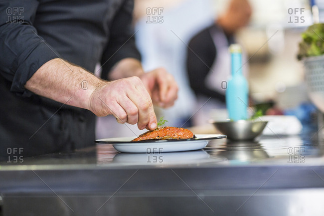 Midsection of chef garnishing food while coworker working in background at restaurant