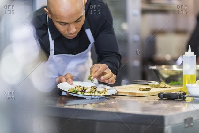 Chef garnishing food in plate at restaurant kitchen