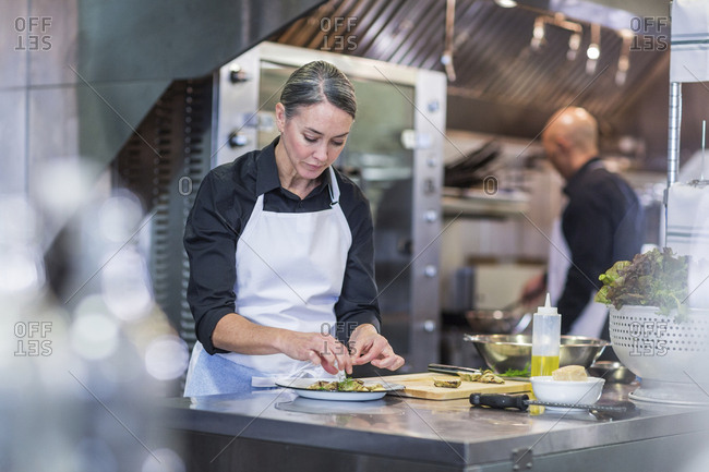 Female chef garnishing food while coworker working in background at restaurant kitchen