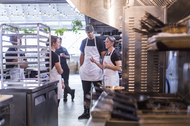 Female chef discussing with coworkers in restaurant kitchen