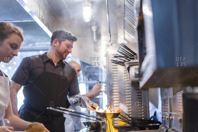 Chefs preparing food in flames in kitchen at restaurant