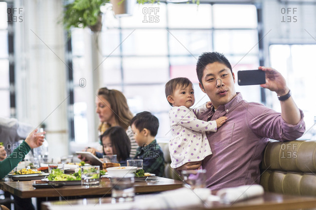 Father taking selfie with baby girl while sitting with family in restaurant