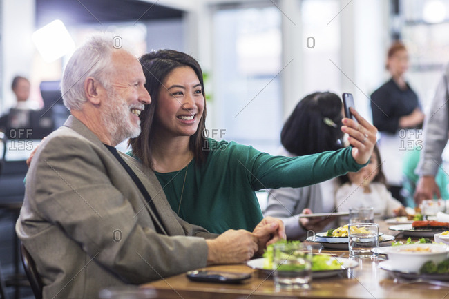 Woman taking selfie with senior man in restaurant