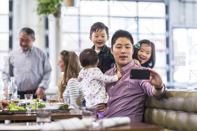 Father taking selfie with children while sitting with family in restaurant
