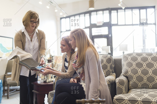 Saleswoman showing fabrics to female customers sitting on armchair in furniture store