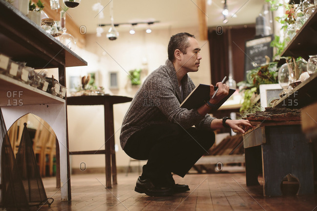 Worker examining plants in garden center