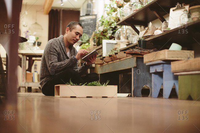 Worker using tablet computer while sitting on floor in plant shop