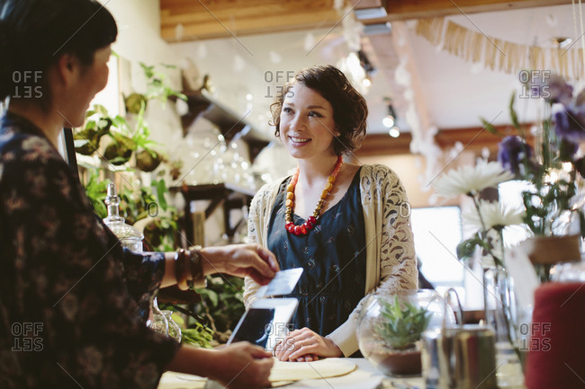 Owner using card reader for payment from customer in plant shop