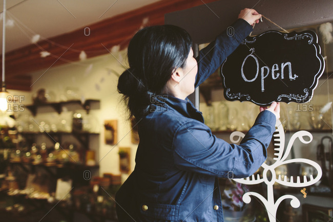 Side view of female owner hanging open sign on door of plant shop