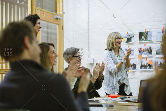 Colleagues clapping in meeting at board room