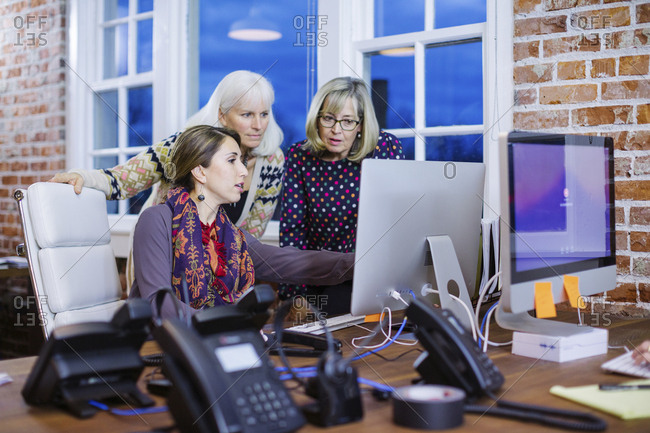 Businesswoman explaining to female colleagues through desktop computer at desk