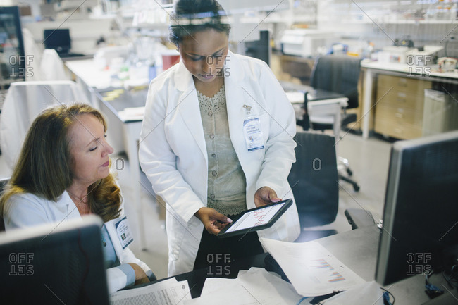 Female doctor showing tablet computer to coworker in medical room seen through glass