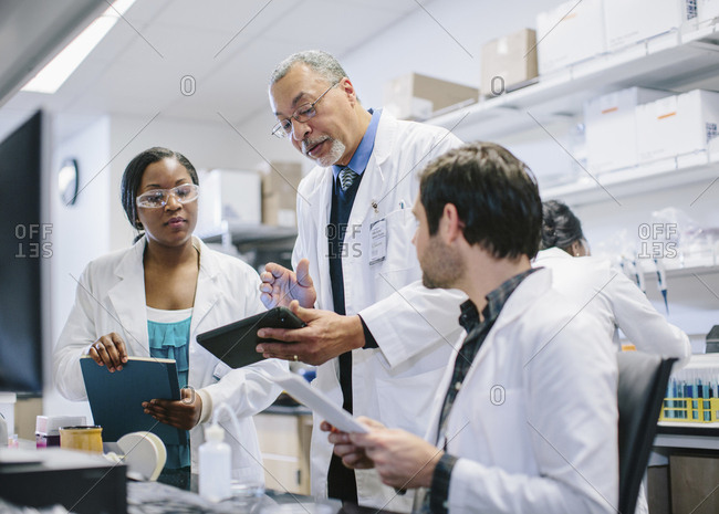 Male doctor discussing medical records with coworkers in hospital