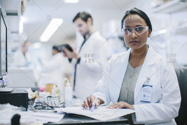 Female doctor looking away while working in hospital with coworkers in background