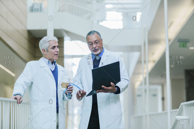 Male doctors discussing over laptop computer in hospital corridor