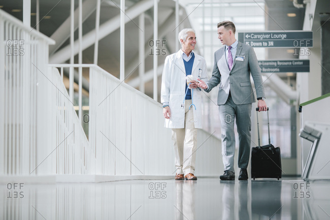 Male doctors talking while walking in hospital corridor