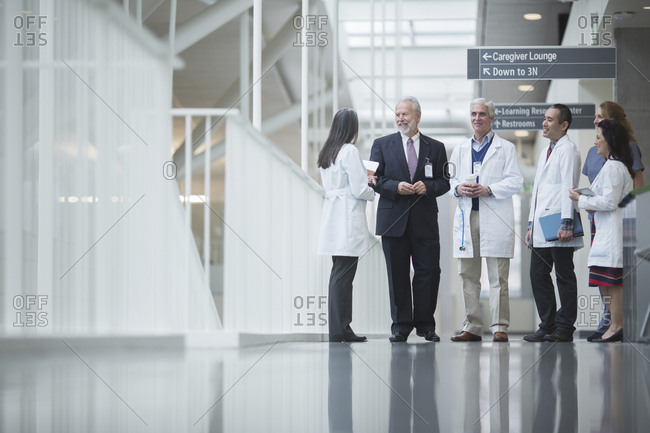 Senior doctor discussing with coworkers while standing in hospital corridor
