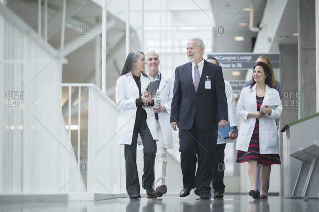 Senior doctor discussing with coworkers while walking in hospital corridor