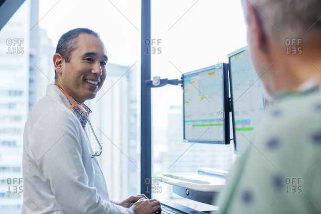 Smiling male doctor talking to patient while using computer in hospital ward