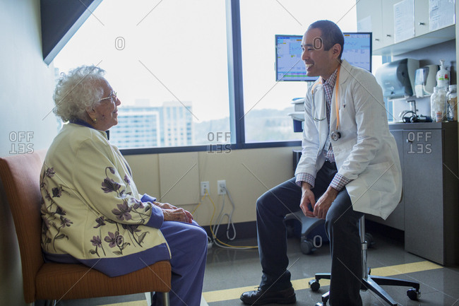 Smiling male doctor talking to patient in hospital ward