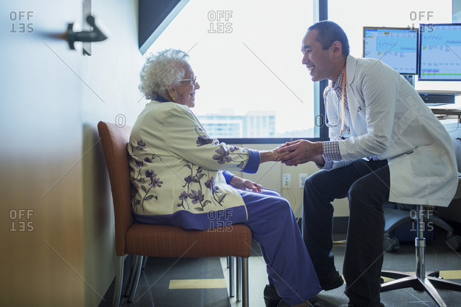 Smiling male doctor holding hand while talking to patient in hospital ward