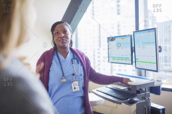 Female doctor looking at patient while standing by desktop computers in medical room